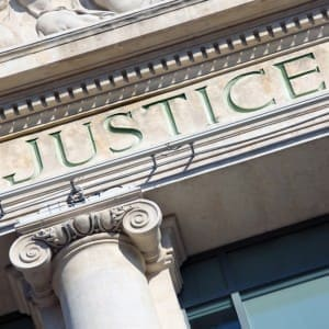The word Justice on a Courtroom Building.