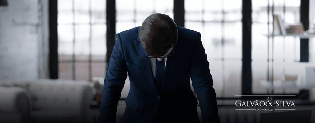 Homem com duas mãos na mesa triste por falência